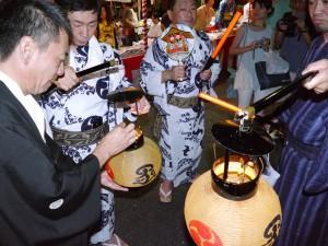 神楽台車列を先導する提灯にロウソクをともす函谷鉾の町方