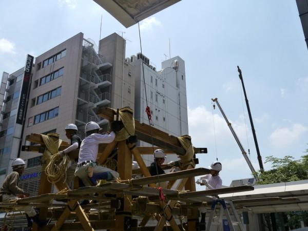 木材、荒縄で職人がくみ上げる鉾の向かいでは、クレーンのオペーレータが、京の一等地にビルを建てようとしていた。